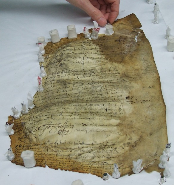 The edges of the parchment are held down with magnets